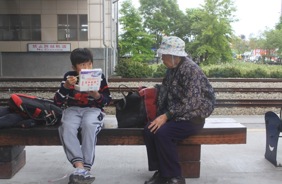 A Young Boy with His Grandmother at a Small Train Station