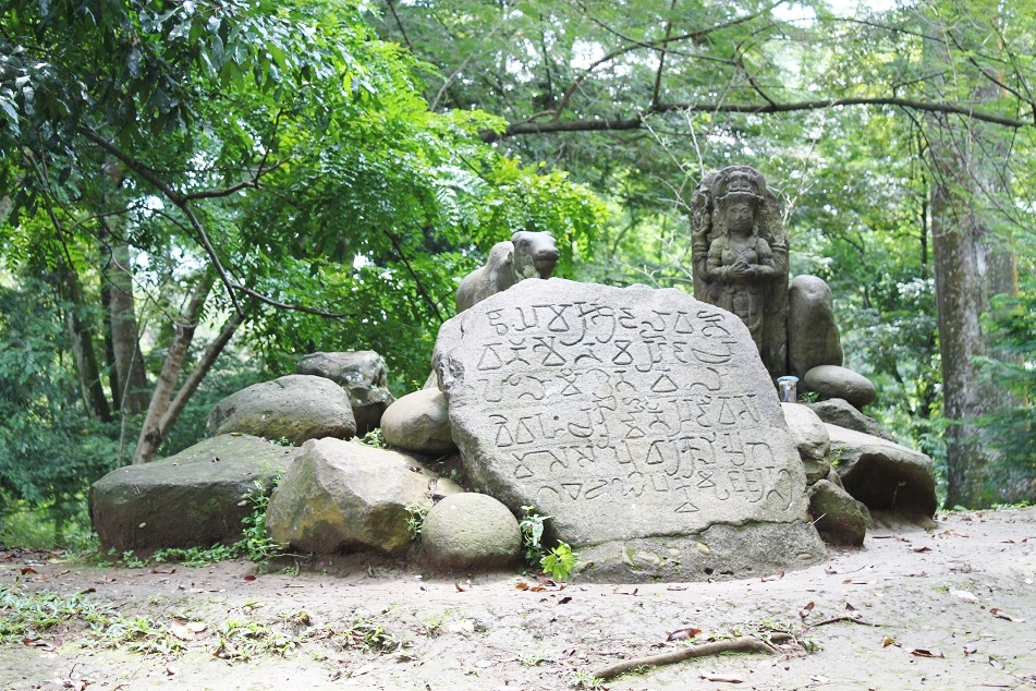 An Ancient Hindu Statue next to A 19th-Century Inscription